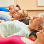 grupo de mujeres de diferentes edades en el suelo practicando ejercicios de respiracion