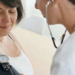 doctora con estetoscopio revisando a mujer la presion alta afecta tu velocidad al caminar