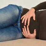 mujer recostada sobre sofa con las manos en su vientre sufriendo de incontinencia