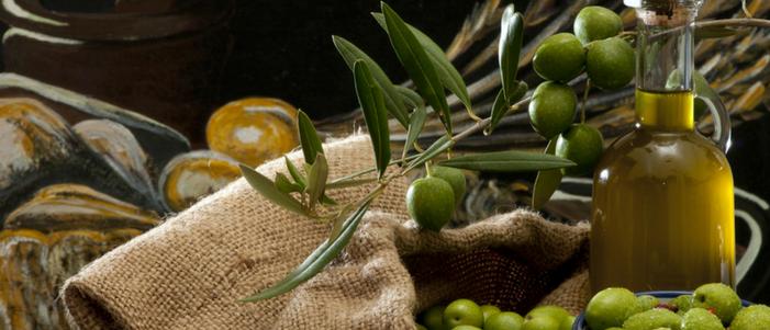 costal cafe con ramo de frutos de arbol de oliva y botella de vidrio con aceite de oliva