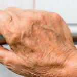 mano de un adulto mayor sosteniendo un barandal bano seguro para adultos mayores