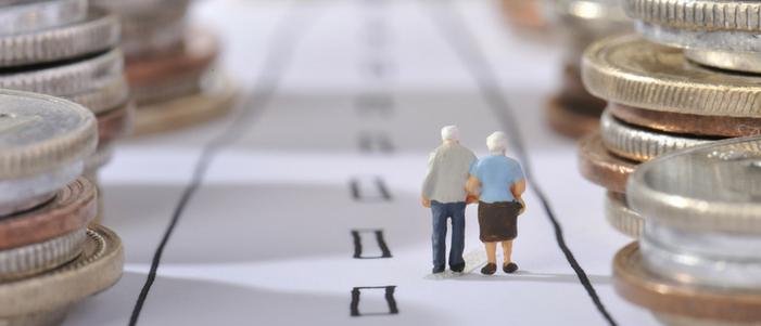 maqueta con munecos de una pareja de adultos mayores y torres de monedas
