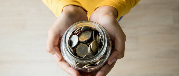 manos de mujer sosteniendo un frasco de vidrio lleno de monedas visto desde arriba