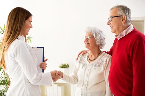 Dos adultos mayores saludando a un doctor