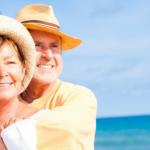 pareja de adultos con sombrero abrazados en la playa disfrutando de sus vacaciones