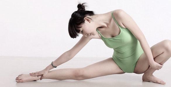 mujer con body color verde realizando estiramientos de piernas el yoga reduce el parkinson