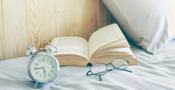 fotografia donde hay cama almohada reloj y libro trucos para descansar por la noche