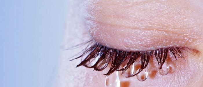fotografia del ojo de una personas se observa que de sus pestanas cuelgan gotas de agua