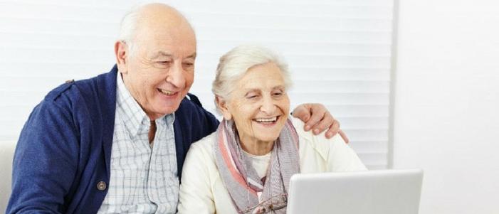 hombre y mujer adultos mayores abrigados sonriendo frente a computadora