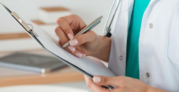 doctora con bata y estetoscopio llenando una formulario con datos personales del paciente