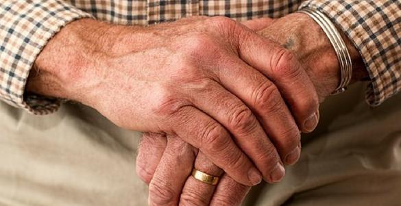 manos de adulto mayor con anillo en su dedo sufriendo los efectos del parkinson