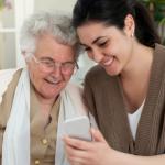 mujer joven junto a mujer de la tercera edad con lentes mirando un celular color blanco