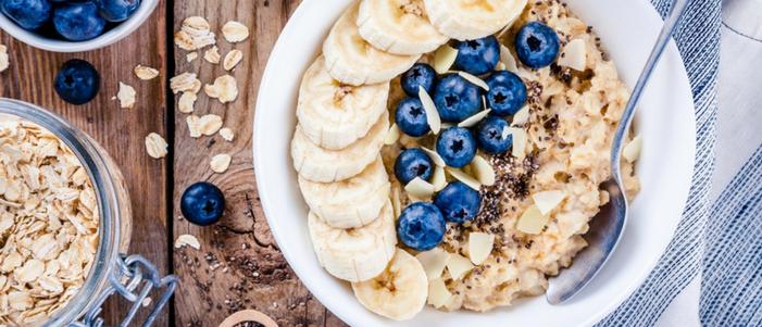 plato con avena platanos y cuchara conoce los beneficios de consumir carbohidratos