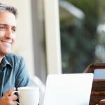 hombre sentado en su sala sonriendo con taza blanca y lap top abierta trabajando en casa