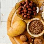 tabla de madera con platos con avena pasas nuez papa y mas alimentos con vitamina b
