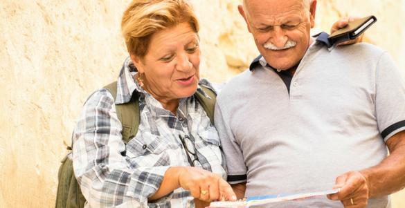 pareja de adultos mayores revisando un mapa conociendo lugares para ir en pareja