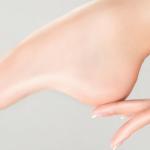 pie femenino con una mano que o acaricia del tobillo que dice de ti las forma de los pies