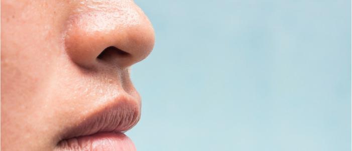fondo azul cielo y parte de la cara de una persona destacan de la nariz y boca