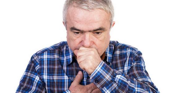 adulto mayor con camisa a cuadros y mano en la boca estos alimentos provocan mal aliento