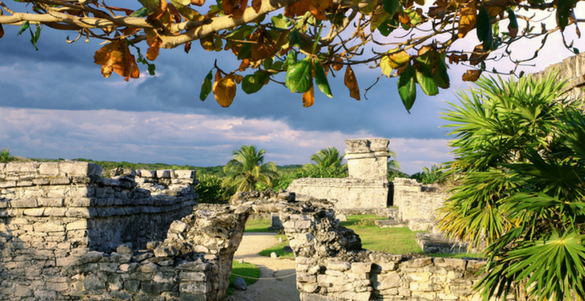 fotografia de la zona arqueologica chichen itza con piramides palmeras y el cielo con nubes