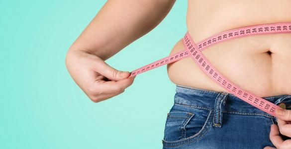 mujer con pantalon de mezclilla y sobrepeso midiendo su cintura con cinta metrica color rosa