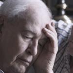 persona mayor canosa con mano en la cabeza mientras otro hombre lo abraza y observa