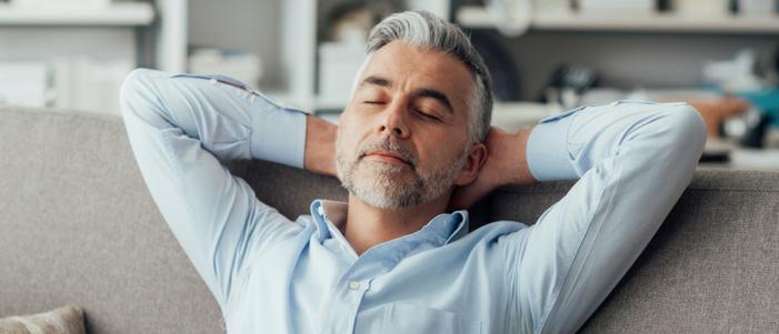 hombre mayor de camisa azul y pelo canoso sentado con las manos en la cabeza y ojos cerrados