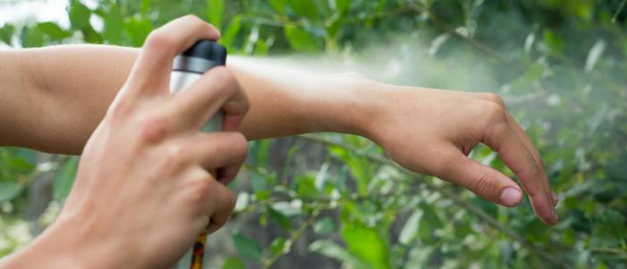 persona rociando repelente de mosquitos en sus manos al fondo plantas verdes