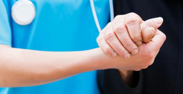 doctor de bata azul y estetoscopio tomando de la mano de un paciente con playera negra