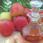 mesa de madera en jardin con diez manzanas rojas recipiente de vidrio con vinagre de manzana
