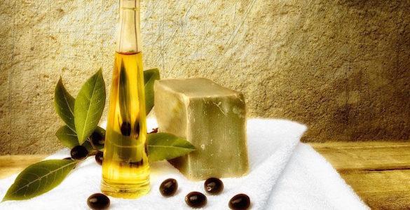 botellas de vidrio sobre una mesa con aceite de oliva y toallas blancas