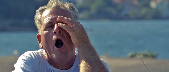 hombre rubio de playera blanca tallando su ojo y bostezando cansancio en adulto mayor