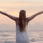 mujer en playa de cabello largo y rubio con vestido blanco y brazos extendidas al cielo