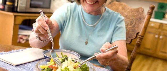 mujer mayor comiendo un plato de ensalada con cubiertos reglas para tener buena digestion