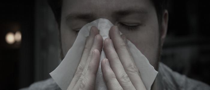 joven con ojos cerrados y panuelo en la nariz usa aceites de esencias para aliviar alergias