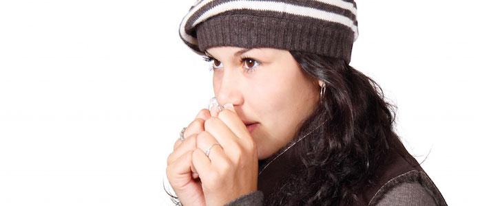 mujer cabello largo con gorro tejido cafe con blanco manos en la boca chaleco y sueter