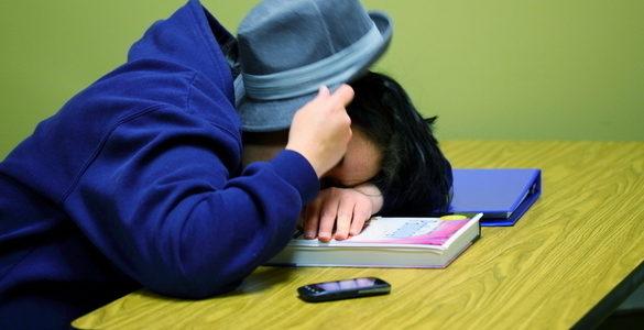 hombre de sudadera azul y sombrero en su rostro dormido sobre libros en mesa de madera