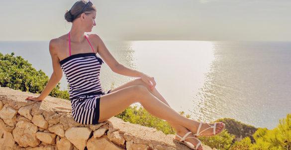mujer sentada con huaraches traje de bano en barda de piedra de fondo el mar