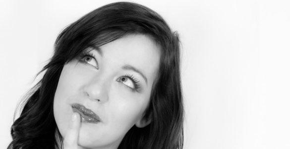 mujer de cabello largo vista a la derecha y dedo en la boca como saber si tienes cancer de vejiga
