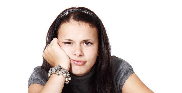 mujer con la mano en la barbilla y pulsera no sabe el remedio casero para eliminar verrugas