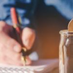 hombre de camisa azul escribiendo en libreta con pluma y metiendo una moneda a un frasco