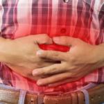 hombre de camisa a cuadros con manos en el estomago enrojecido sintoma de la gastritis