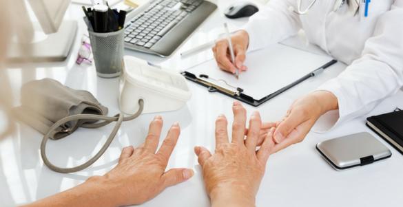 escritorio de un doctoe con libreta pluma y teclado tomado de la mano a su paciente