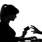 mujer con tarjeta de credito en su mano frente a computadora con mano saliendo de pantalla