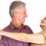 pareja de adultos mayores el con camisa blanca y ella con blusa cafe bailando