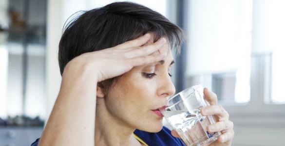 mujer con la mano sobre su cabeza tomando agua conoce los sintomas de la menopausia
