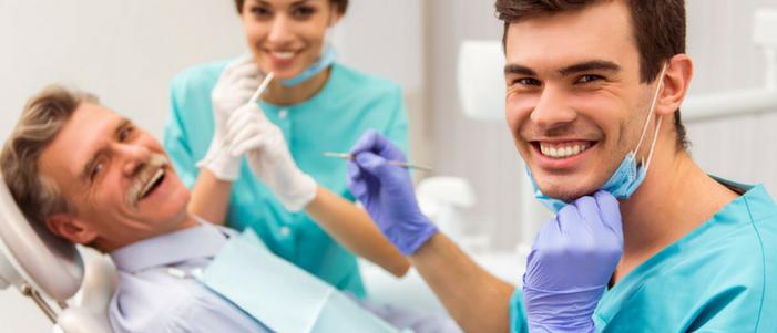 dos dentistas y un adulto mayor de bigote en revisión de sus dientes recostado sonriendo