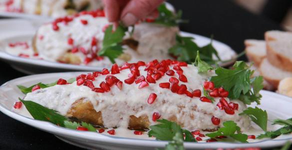 plato con chile en nogada granada y una mano colocandole perejil