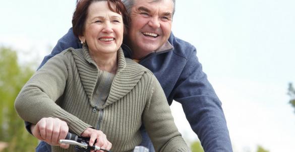 pareja adulta dando paseo en bicicleta sonriendo beneficios de la actividad fisica en adultos