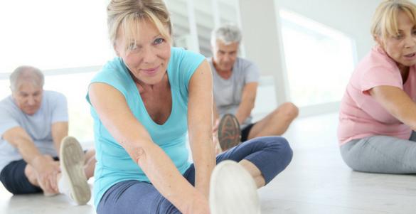 grupo de cuatro adultos mayores dos mujeres y dos hombres realizando ejercicios de yoga